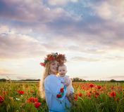 Inspired young mother. Happy motherhood, a young women in a wildflower wreath with her little daughter walking in the poppy field on a sunset. Inspired nature Stock Image