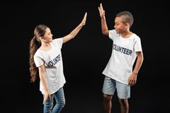 Inspired young volunteers giving a high-five. Great team. Delighted lovely little volunteers wearing white shirts and giving a high-five Stock Photos