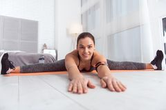 Inspired young woman doing sports at home. I love exercising. Beautiful joyful fit dark-haired young woman smiling and stretching while sitting on the carpet Stock Images