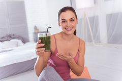 Inspired young woman holding a glass of juice. I adore juice. Good-looking exuberant athletic dark-haired young woman smiling and holding a glass of fresh juice Stock Photo