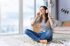 Inspired young woman listening the music at home. Enjoyable tunes and melodies. Delighted inspired peaceful woman sitting at home and listening the music while Stock Photos