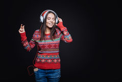 Inspired young woman listening to the music. Peaceful tune. Smiling inspired involved girl standing against the black background while expressing peacefulness Stock Image