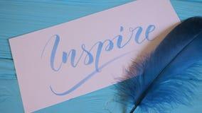Inspireer tekst Mooie doopvont van het van letters voorzien motievenwoord op wit canvas met blauwe inkt Achtergrond Grafisch Ontw stock videobeelden