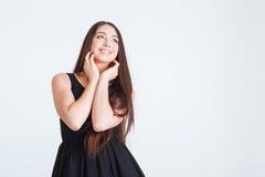 Inspirerad attraktiv ung kvinna med långt anseende och drömma för hår Arkivbild