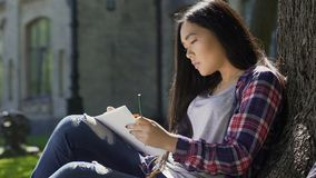 Inspirerad ung asiatisk kvinnlig konstnärteckning utomhus, student som tycker om hobby arkivfilmer