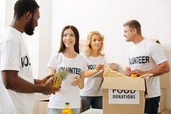 Inspirerade volontärer som arbetar på en annan sändning av foods Royaltyfri Fotografi