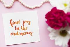Inspirerande citationsteckenfyndglädje i det vanliga som är skriftlig i kalligrafistil med vattenfärgen Sammansättning på en rosa Arkivfoto
