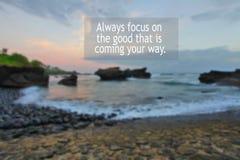 Inspirierend Motivdes zitats Fokus immer auf dem guten, das Ihre Weise kommt Mit undeutlichem Hintergrund des felsigen Strandes L lizenzfreie stockfotografie
