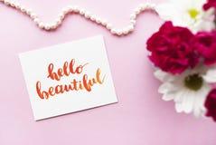 Inspirierend Zitathallo schönes geschrieben in Kalligraphieart mit Aquarell Zusammensetzung auf einem rosa Hintergrund Flache Lag Stockbilder
