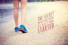 Inspirierend Zitatplakat auf Frauen ` s Beinen, die auf Strand laufen Lizenzfreie Stockfotografie