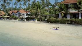 Woman Does Yoga on Empty Beach at House Upper View. Inspiring aerial view young athletic woman in black does yoga exercises on empty beach at beautiful resort stock footage