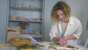 Inspiring atmosphere, creative potter girl shapes clay product with pleasure on table in workroom stock video footage