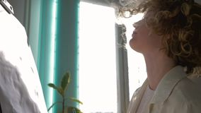 Inspiring atmosphere, professional artist woman with paintbrush enjoying painting picture on easel at workroom in. Natural light against bright window in sun stock video