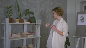 Inspiring atmosphere, young potter female drink hot tea from cup while working in clay crafting workshop. Camera movement stock video footage