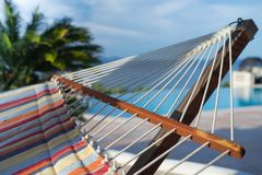 Take rest and have nap. Inspiring colorful picture of hammock hanging near big green palm. May be used as a background for quotes and cover image Royalty Free Stock Photos