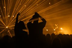 Inspiring concert. Silhouettes of an ardent couple at a music concert with a spectacular laser show royalty free stock photo