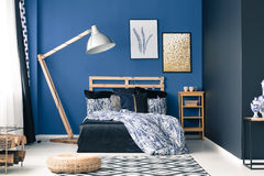 Inspiring cyan bedroom. With wooden stylish lamp stock photography