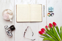 Inspiring desktop of girl`s working as writer. Opened diary and pen, vintage camera, a bouquet of red tulips and Royalty Free Stock Image