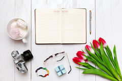 Inspiring desktop of girl`s working as writer. Opened diary and pen, vintage camera, a bouquet of red tulips and Stock Photography