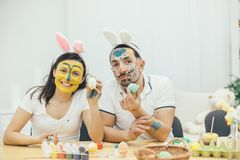 Inspiring Mother and father showing easter eggs at the camera. Their faces and hands are in paint. Bunny ears on their royalty free stock images