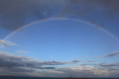 Inspiring Rainbow Portal. An enormous rainbow spans a bright blue sky,with rainclouds above and below Stock Photography