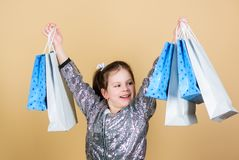 Inspiring store to buy more. Girl with shopping bags beige background. Shopping and purchase. Black friday. Sale. Discount. Shopping day. Child hold bunch royalty free stock photography