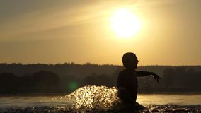 Happy man raises the lake water to entertain at sunset in slo-mo. An inspiring view of a happy young man who raises his hands with water to entertain and to make stock video footage