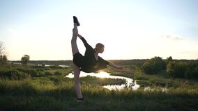 Stretchy girl bending forward and doing a front split like a windy sail at sunset in slo-mo. Inspiring view of a springy fair-haired girl in shorts bending stock video footage