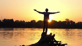 Encouraged man stands on tree roots on a lake bank in slo-mo. An inspiring view of a young man who stands on tree roots and keeps his hands aside on a forest stock footage