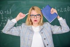 Inspirowa? pedagog iskrow? motywacj? Pedagog kobiety chwyta ksi??ki i pi?ra chalkboard t?o tutaj szuka? zdjęcie stock