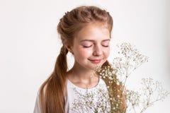 Inspirowana spokojna mała dziewczynka wącha perfumowanie kwiaty fotografia royalty free
