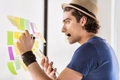 Inspirowany męski freelancer robi notatkom na papierze Obraz Stock