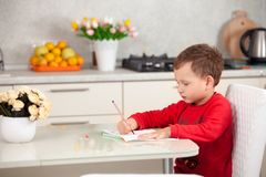 Inspirujący chłopiec rysuje obrazek na papierze przy stołem zdjęcie royalty free