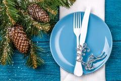 Inställning för jultabellställe - blå tabell med den vita servetten, blåttplattan, den vita gaffeln och kniven, dekorerat julträd Royaltyfri Foto
