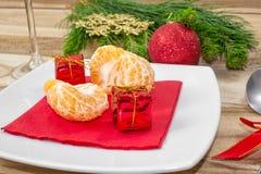 Inställning för jultabellställe festlig bakgrund Filialer av gran, bollar, bestick och tangerin royaltyfria foton