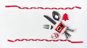 Inställning för jultabellställe med bestick, röd bandram och garnering, kopieringsutrymme på vit skrivbords- bakgrund, bästa sikt arkivfoto