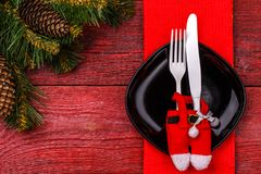 Inställning för jultabellställe med den röda servetten, svart platta, vit gaffel och kniv, dekorerade jultomtenflåsanden och jul Arkivbild