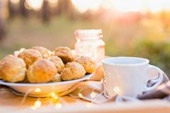 Inställning för kaffetabell med kaffekoppen, kakor på solnedgången arkivbilder
