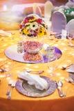 Inställning för matställetabell med ljus garnering under tabellen med bukettgarnering Royaltyfri Foto