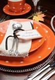 Inställning för ställe för tacksägelsematställetabell med apelsinplattor och den lyckliga tacksägelseetiketten - lodlinje. Royaltyfri Fotografi