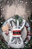 Inställning för ställe för julmatställetabell med plattan, bestick, granfilialer, snö, tom övre etikettsåtlöje och snögubben på l Arkivbild