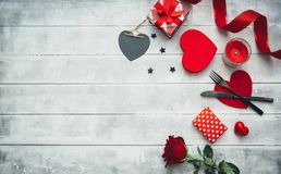 Inställning för valentindagtabell med gaffeln, kniven, röda hjärtor, bandet och rosor royaltyfria foton