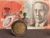 inställning till det europeiska myntet av två euro och bakgrund med den australiska sedeln av tjugo dollar royaltyfri fotografi