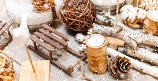Inställningen för jultabellstället med jul sörjer kottar, trägarneringar, bokeh, snöflingor fotografering för bildbyråer