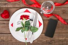 Inställningen för tabellen för matställen för dagen för valentin` s med det röda bandet, rosen, kniven och gaffeln ringer över ek Royaltyfri Fotografi