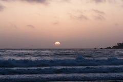 Inställningssol i molnig himmel med havvågor Fotografering för Bildbyråer