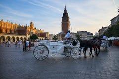 Inställningssol på staden Hall Tower och torkduken Hall på marknadsfyrkant i Krakow Polen Royaltyfri Foto