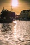 Inställningssol som reflekterar i vattnet av handfatet för golfhamnstad som vätskeguld royaltyfri bild