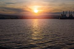 Inställningssolen reflekterar i vattnet av hamnstaden royaltyfri foto