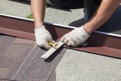 Instaalation natural de la teja de tejado El trabajador del constructor del Roofer marca la distancia entre las costuras imagen de archivo libre de regalías